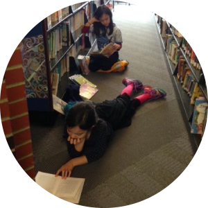 Two children reading in the stacks at the downtown library